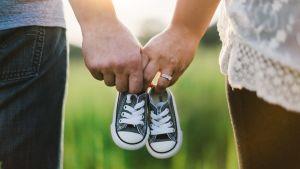 föräldrar hållar i babyskor