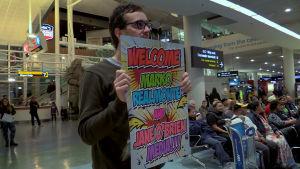 David Farrier odottaa lentokentällä. Kuva Farrierin dokumenttielokuvasta Tickled.