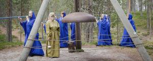 Metsässä sinisiin kaapuihin pukeutuneita naisia, soittavat sinisiä huiluja, keskellä ison kirkonkellon äärellä vihreäkaapuinen nainen naamio kasvoilla. Soivan Metsän Ilmattaria.