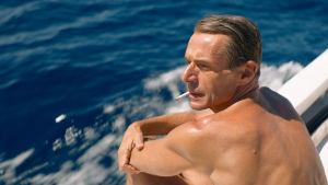 En brunbränd Jacques sitter och röker ombord på en motorbåt.
