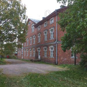 En rödtegelbyggnad i 2-3 våningar, en gammal arbetarkasern i Billnäs bruk. Gräsplan, grusgång, lövträd.