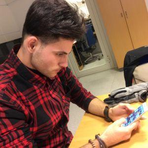 En ung man tittar på sin telefonskärm.