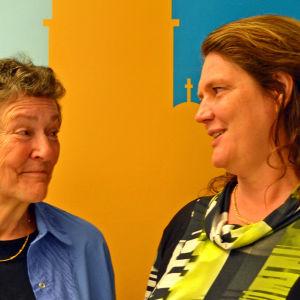 Elisabeth Helander (SDP, t.v.) och Veronica Hertzberg (SFP, t.h.) poserar framför en vägg.