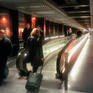 Kvinna går med kappsäck på löpande band på flygplats