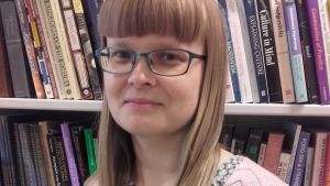 Sofia Sjö poserar framför en bokhylla