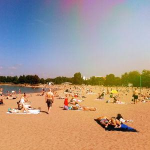 Sandudds simstrand är full av människor som njuter av det varma vädret.