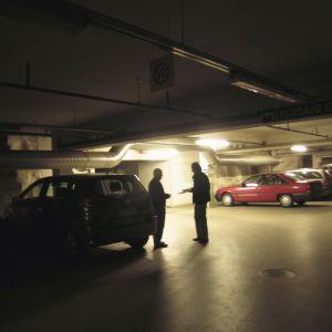 Två män byter varor i en parkeringshall