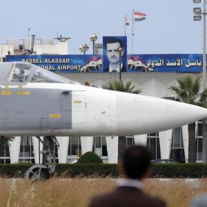 Ett ryskt jaktplan av typen Su-24 passerar ett porträtt på Syriens president Bashar al-Assad på flygbasen Hmeimym i Latakia 4.5.2016