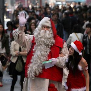 En finländsk julgubbe i Hongkong vinkar med handen.