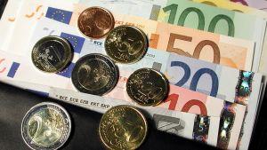 Sedlar och mynt i en hög.