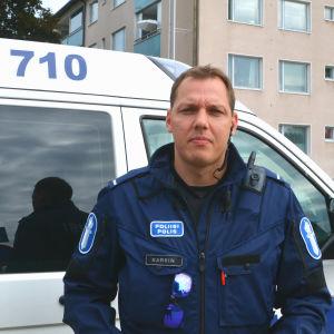 Man i polisuniform står framför polisbil.