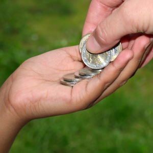 En hand som överräcker mynt till en annan hand.