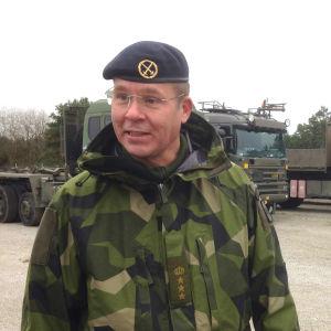 Mattias Ardin, leende, ser förbi kameran, militära lastbilar i bakgrunden.