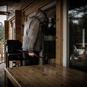 Inbrottstjuv tittar in genom stugfönster