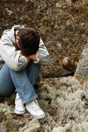 En kvinna sitter med huvudet nedböjt dolt i armarna klädd i grå jacka, blåa jeans och vita fritidsskor på ett stenblock i naturen.