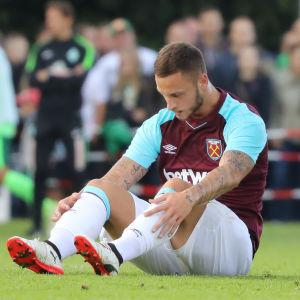 West Ham-spelaren Marko Arnautovic sitter på planen och ser nedstämd ut.