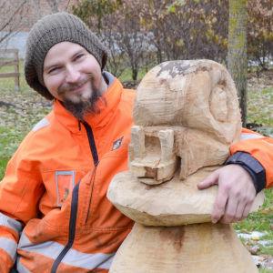 Niko Nordström ler och har armen runt en skulptur av en snigel som sitter på en sopp.