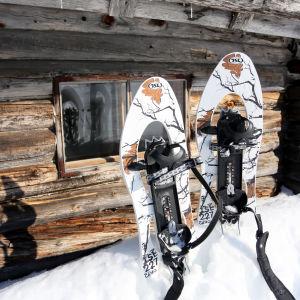 Lumikengät hangessa pystyssä hirsimökin edustalla.
