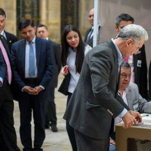 Colombias expresident Álvaro Uribe (till höger) och partiets presidentkandidat Iván Duque (till vänster) i en vallokal i Bogota på söndagen.