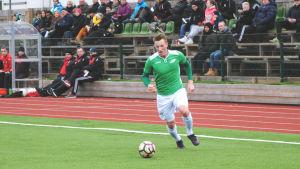 EIF:s Theo Lundström springer med bollen på fotbollsplanen.
