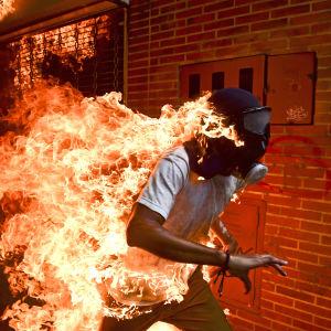 En man i gasmask springer, hans t-tröja har fattat eld.