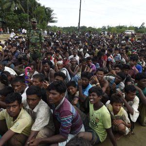 Burmesiska Rohingya-flyktingar väntar på mat i ett flyktingläger i Bangladesh.