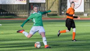 En ung kvinna i vita shorts och grön tröja spelar fotboll i Ekenäs IF. Hon heter Rebecka Mannström.