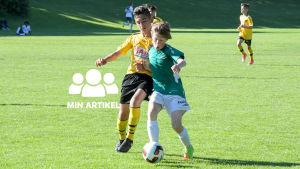 Två pojkar som spelar fotboll.