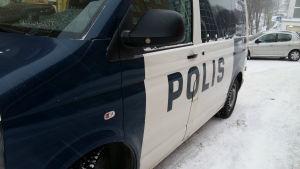 En polisbil har stannat på en snöig gata.