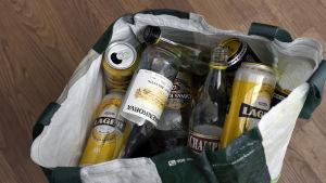 Tomma alkoholflaskor i en kasse.
