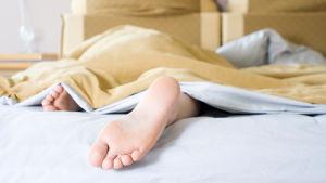 Bara fötter som sticker ut under sängtäcket.