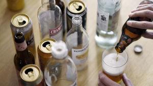 Alkoholflaskor och burkar på ett bord.