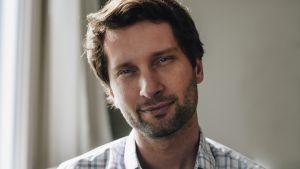 Porträtt av Michal Kosinski med rågblont hår, kort skägg och en vit skjorta med gråblåa rutor.