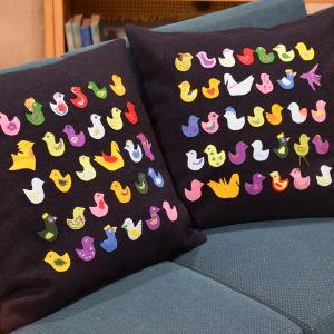 Två kuddar med färgglada fåglar i en soffa