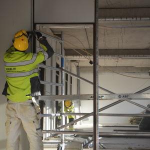 Byggarbetare river ner gamla väggar i ett hus.