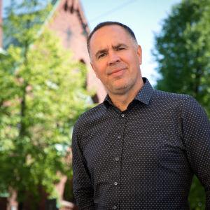 Jens Berg mot bakgrund av en kyrkofasad i rödtegel.