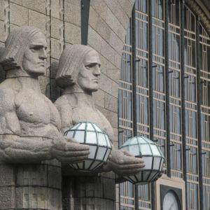 """Helsingin rautatieasema. """"Lyhdynkantajat"""" (Emil Wikström, 1914), valaisimia kannattelevat patsaat Helsingin rautatieaseman pääsisäänkäynnin vieressä."""