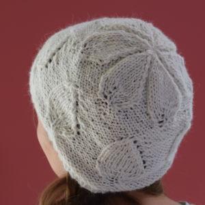 Handstickad mössa med bladmönster på ett huvud