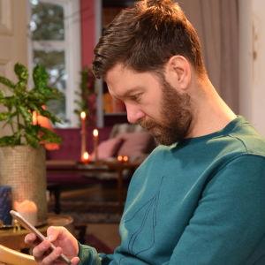 Mies katsoo puhelintaaan niska kyyryssä.