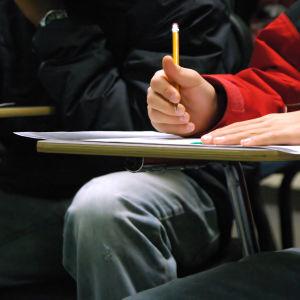 Person gör anteckningar med penna och papper.