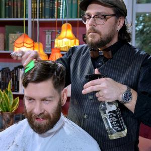 En man klipper en annan mans hår.