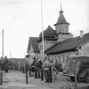 Jatkosota. Karhumäki, Itä-Karjala. Karhumäen rautatieasema. Eino Nurmi (oikealla) asemarakennuksen edustalla. Sotilaita ja lähdössä oleva sotilasjuna asemalla.