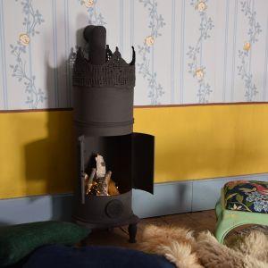 En liten kamin gjord av återvunnet material med ljusslinga istället för eld.