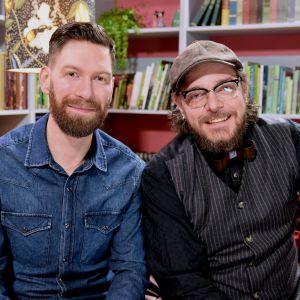Två leende män med skägg.