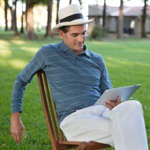 En man sitter ute och läser en e-bok.