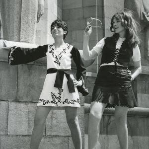 Två kvinnor klädda i minikjol poserar vid en stenvägg 1960-tal.