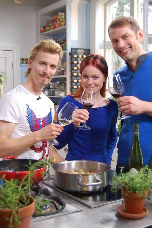 En man, kvinna och man står i rad och skålar med vinglas.