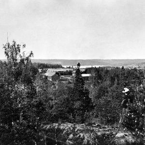 I. K. Inhan valokuvassa Inhan Saima-sisar kotivuorella, taustalla Valkeajärven talo Jäähdyspohjassa Virroilla