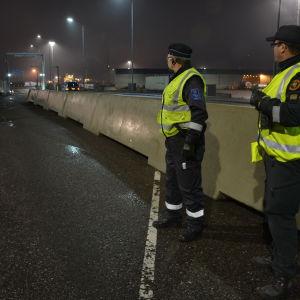 Pertti Rönkkö från tullen och Rabbe Wikholm från gränsbevakningen väntar på att långtradarna ska komma ut från morgonens första fartyg i Hangö.