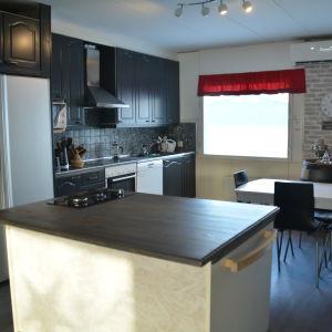 En vy över ett kök med mörka skåpluckor. På bilden syns också ett matbord och en köksö.